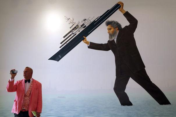 """Nel Giugno 2011, uno yacht lungo 115 metri di nome """"Luna"""" era parcheggiato lungo il molo dei Giardini dove si trova la Biennale, bloccandone la visuale. Il Panfilo, in quella posizione, limitava il transito di abitanti e visitatori. Quest'atto ha fatto infuriare William Morris (quello ritratto sulla parete con una nave per le mani), un designer socialista di epoca vittoriana che, sebbene morto da tempo, è tornato, trasformato in colosso, e ha scaraventato lo yacht nella laguna."""