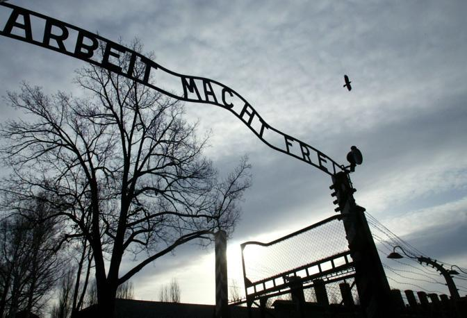 A file photo of a bird flying above a gate of the Auschwitz Museum